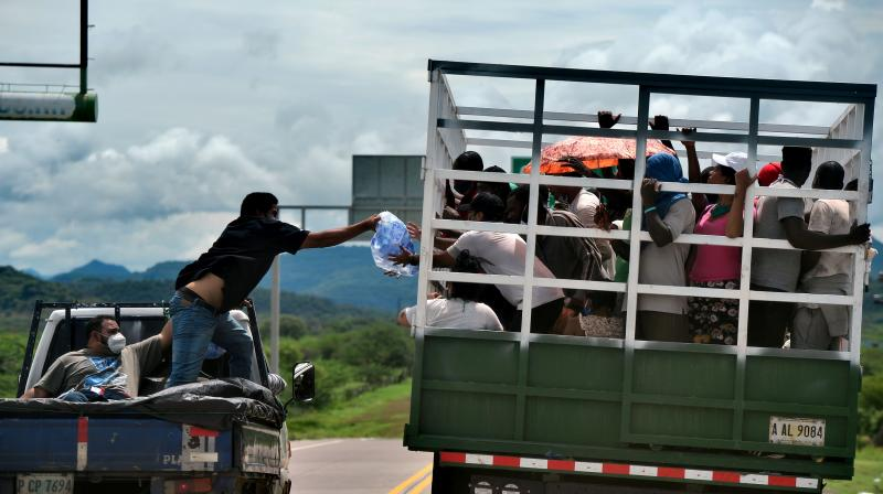 A man gives water to migrants heading in a caravan to the border with Guatemala as they travel onboard a truck in Cerro Hula, 10 km south of Tegucigalpa. (AFP)