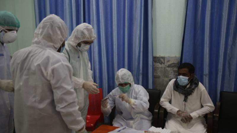 Health officials in protective gear take a sample from a man at a screening and testing facility for COVID-19 in Peshawar, Pakistan. (AP)