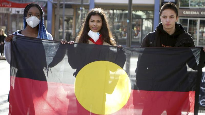 Protesters hold an Aboriginal flag in Canberra, Australia. (AP)