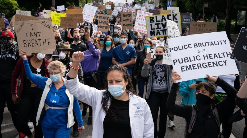 Healthcare workers and others march to Seattle City Hall during the Doctors For Justice event on June 6, 2020 in Seattle, Washington. (AFP)