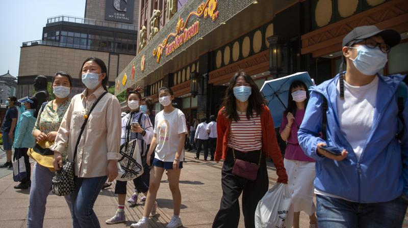 People wearing face masks to protect against the new coronavirus walk outside of a shopping mall at a pedestran shopping street in Beijing. (AP)