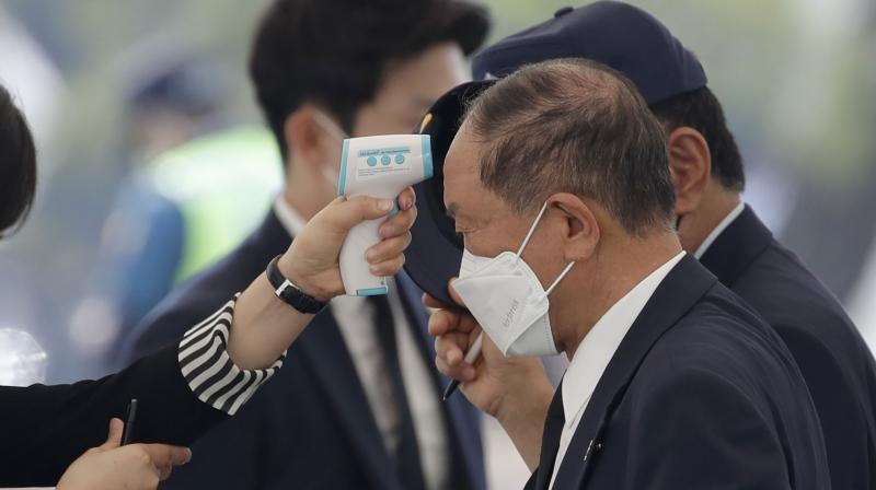 A man wearing a face mask has his temperature checked upon his arrival to attend at Memorial Day ceremony at the national cemetery in Daejeon, South Korea. (AP)