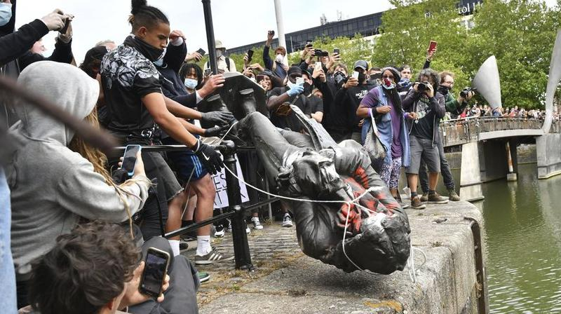Protesters throw a statue of slave trader Edward Colston into Bristol harbour, during a Black Lives Matter protest rally, in Bristol, England. (AP)