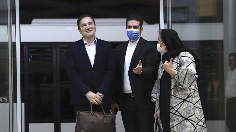 Matteo Taerri, left, is welcomed by an Iranian Foreign Ministry official as his wife stands at right, upon arrival at Tehran's Imam Khomeini Airport from the U.S. (AP)