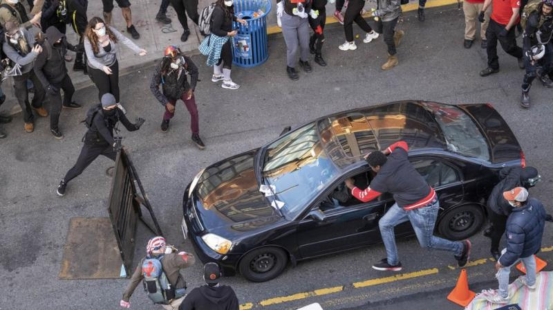 A man drives into the crowd at 11th and Pike, injuring at least one person, before exiting the car and brandishing an apparent firearm. (AP)