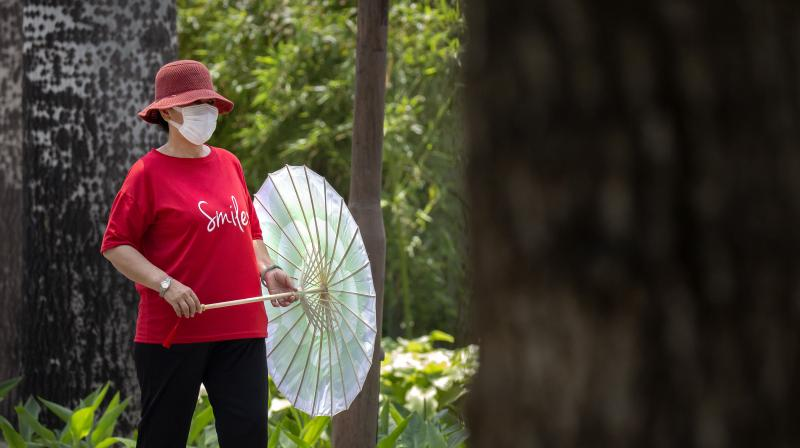 A woman wearing a face mask to protect against the new coronavirus dances with a parasol at a public park in Beijing. (AP)
