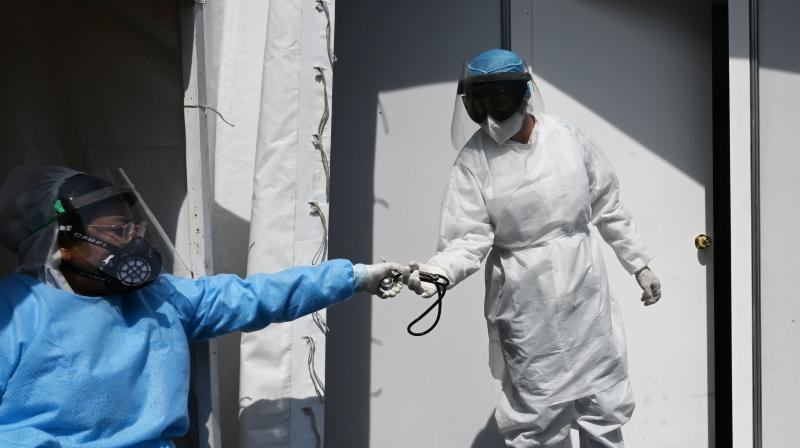 Health workers wearing protective gear are seen at the Central de Abastos market in Mexico City. (AFP)