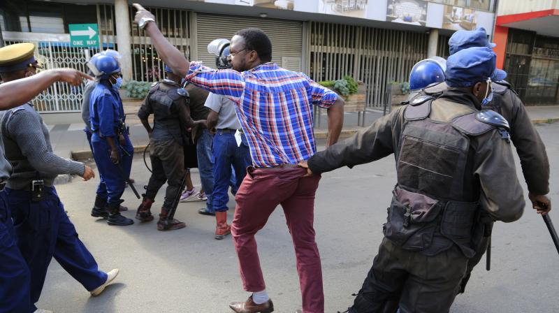 Zimbabwe police arrest opposition supporters outside their party headquarters in Harare. (AP)