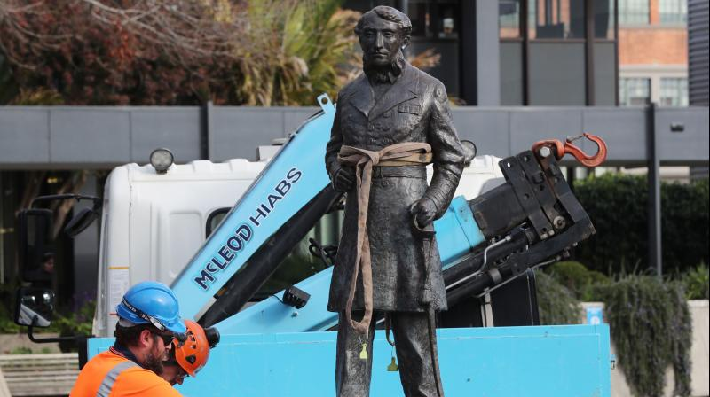Workers remove a controversial statue of Captain John Fane Charles Hamilton from Civic Square in Hamilton on June 12, 2020, following a formal request by the Waikato-Tainui iwi (tribal confederation) and threats it would be torn down during a Black Lives Matter march due to take place the following day. (AFP)
