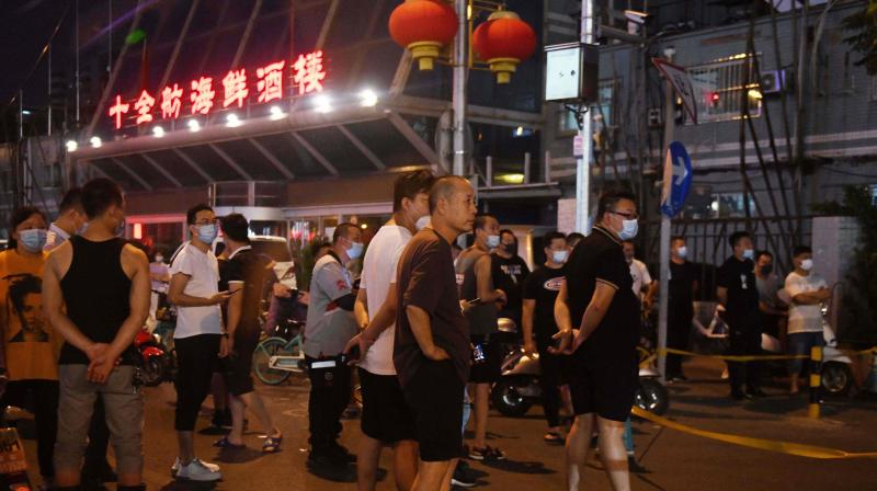 People gather on the street outside the closed Jingshen seafood market in Beijing on June 12, 2020. - Beijing's Xinfadi meat wholesale market and Jingshen seafood market were closed for disinfection and environmental sample collection after it emerged both were visited by two newly identified coronavirus patients, local media reported. (AFP)