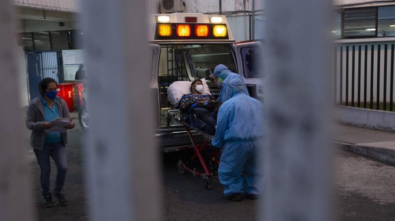 A patient with symptoms related to COVID-19 is brought to the coronavirus unit at San Juan de Dios hospital by firefighters in protective gear in Guatemala City. (AP)