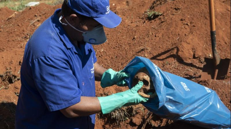 A cemetery worker puts a cranium into a bag while exhuming the body of a person buried three years ago at the Vila Formosa cemetery in Sao Paulo. (AP)