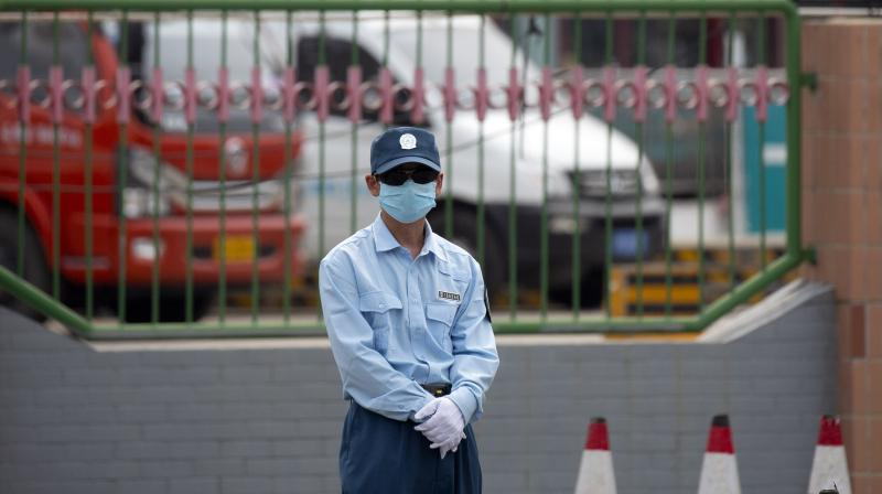 A security officer stands guard outside the Xinfadi wholesale food market district in Beijing. (AP)