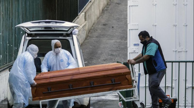 Employees of a funeral parlour carry the coffin of a COVID-19 victim into a vehicle, outside the Carlos Van Buren Hospital in Valparaiso. (AFP)