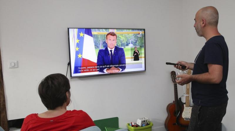 A family watches French President Emmanuel Macron during his televised address, in Bayonne, southwestern France, Sunday, June 14, 2020. (AP)