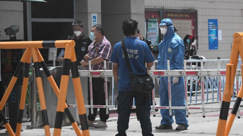 security personnel wearing a protective suit stands guard at a residential area under lockdown near Yuquan East Market in Beijing on June 15, 2020.(AFP)