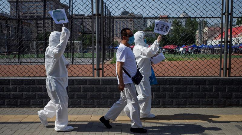 Medical staff members (R and L) in full protective gear carry signs to assist people who live near or who have visited the Xinfadi Market, a wholesale food market where a new COVID-19 coronavirus cluster has emerged, for testing at the Guang'an sports centre in Beijing on June 16, 2020.(AFP)