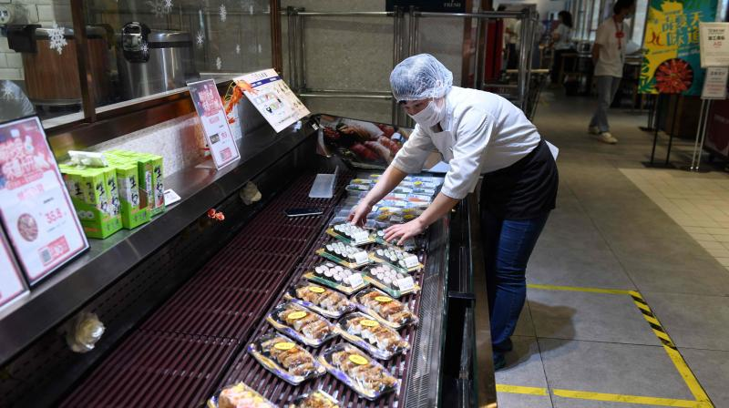 A worker places trays of food in the seafood section of a supermarket in Beijing on June 17, 2020. (AFP)