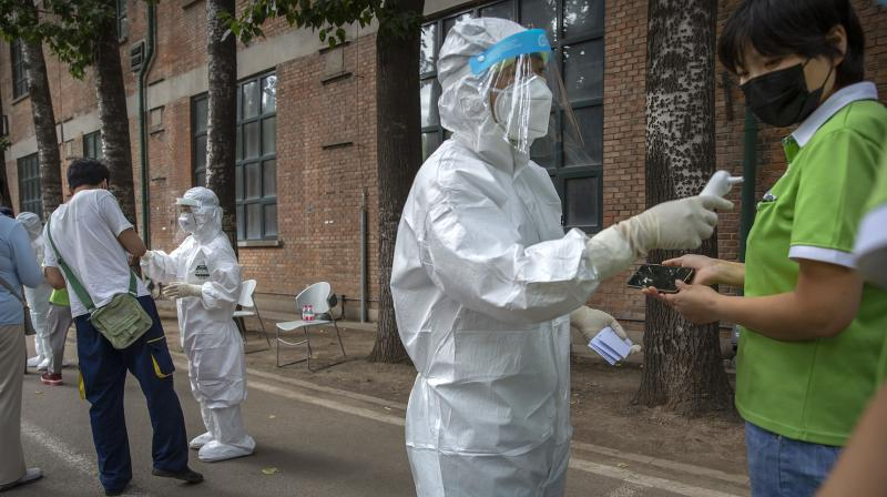 Workers in protective suits take the temperatures of people at a COVID-19 testing site. (AP)