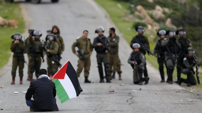 A Palestinian demonstrator holds national flag in front of Israeli forces as they protest against President Donald Trump's Mideast initiative, in Jordan Valley in the West Bank. (AP)