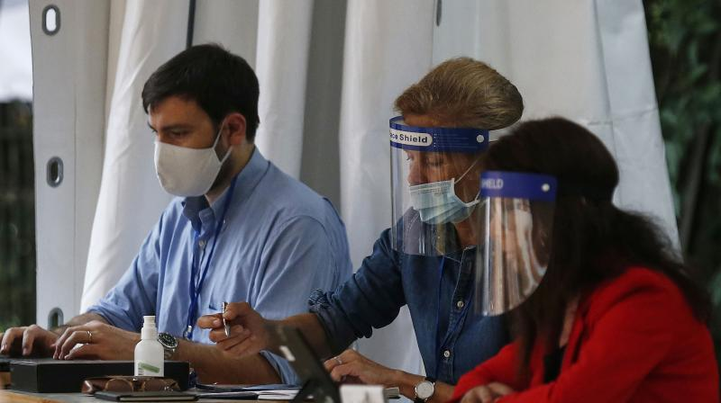 Examiners wear face shields and masks to prevent the spread of COVID-19, during end of year secondary school exams at high school Liceo Kennedy, in Rome. (AP)