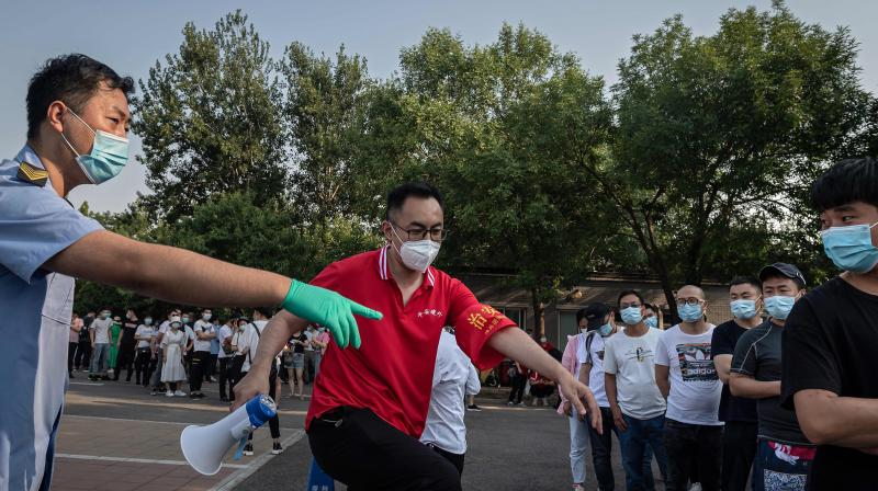 Workers (L and C) guide a group of people wearing face masks as they wait in a queue to test for COVID-19 coronavirus, in Beijing on June 19, 2020. (AFP)