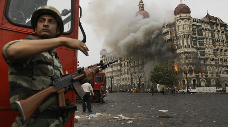 In this November 29, 2008 photo, an Indian soldier takes cover as the Taj Mahal hotel burns during gun battle between Indian military and militants inside the hotel in Mumbai, India. (AP)