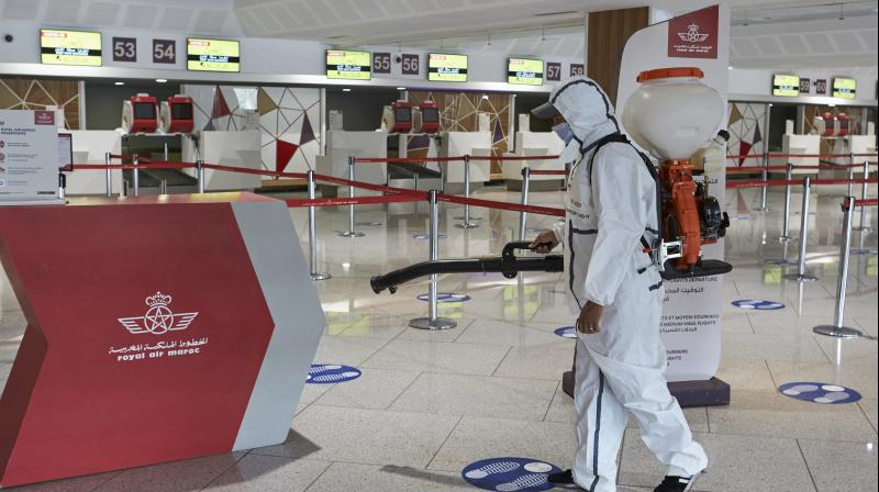 Employee wearing masks as he disinfect to avoid contamination with the COVID-19 virus at the Mohammed V airport in Casablanca, Morocco. (AP)