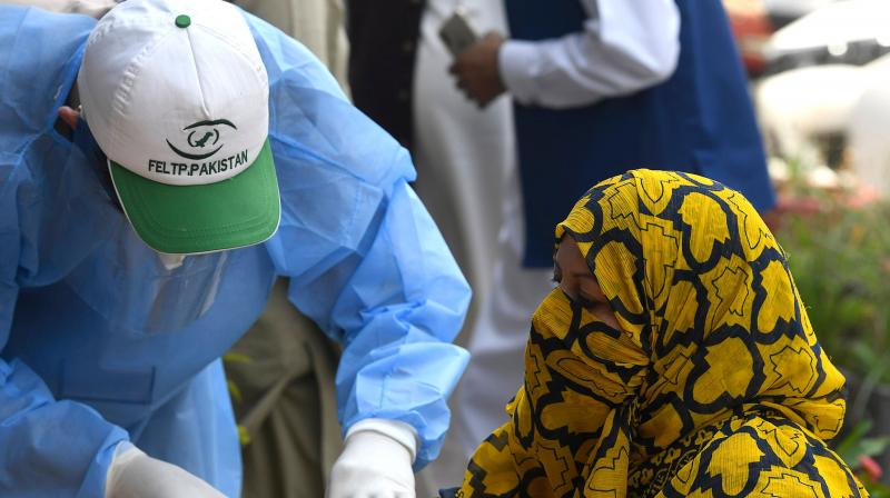A health official wearing protective gear takes a blood sample of a woman at a screening and testing facility point for the COVID-19 coronavirus, alongside a street in Islamabad. (AFP)