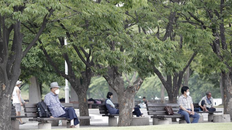 Visitors wearing face masks to prevent the spread of the new coronavirus sit on benches while maintaining social distancing at a park in Seoul, South Korea, Saturday, June 20, 2020. (AP)