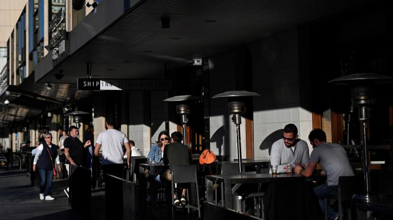 Customers sit at a bar in Sydney. (AFP)