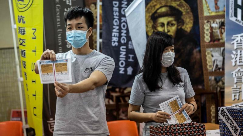 A volunteer (R) holds up a ballot paper during counting in Hong Kong on June 20, 2020, following a vote organised by selection of pro-democracy unions to ask members if they will participate in a city wide strike and if they supported Chinas plans to impose a new national security law in Hong Kong. (AFP)