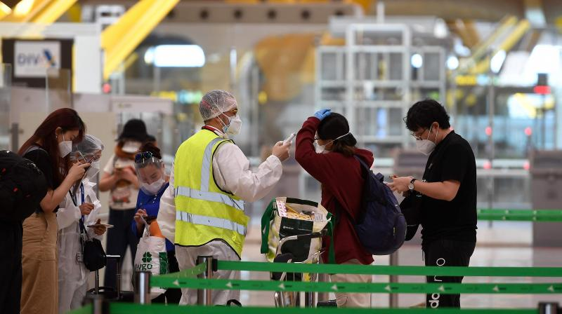 An employee in full protective gear checks the temperature of passengers arriving to check in for their flight bound for Beijing at the Barajas airport in Madrid on June 20, 2020. (AFP)