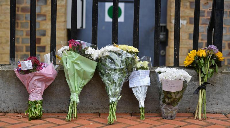Floral tributes are seen at a police cordon at the Abbey Gateway near Forbury Gardens park in Reading, west of London, on June 21, 2020 following a fatal stabbing incident the previous day. (AFP)