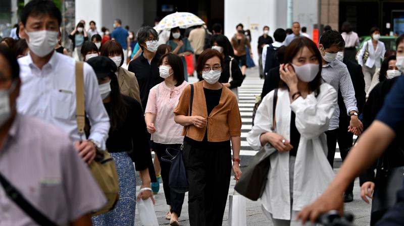Pedestrians wearing face masks cross the street in the Ginza area in Tokyo. (AFP)