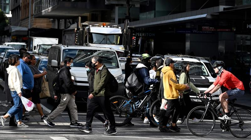 People cross a traffic intersection in the central business district of Sydney. (AFP)
