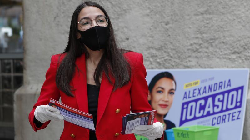 First-term U.S. Rep. Alexandria Ocasio-Cortez, D-New York, awaits passersby as she hands out leaflets explaining how to vote early or by absentee ballot during a stop at the Parkchester subway station in the Bronx borough of New York. (AP)