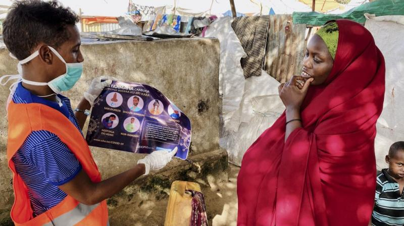 In this photo taken Wednesday, June 10, 2020, an internally-displaced Somali woman, right, is informed how to protect herself from the coronavirus, at the Weydow IDP camp in Mogadishu, Somalia. (AP)