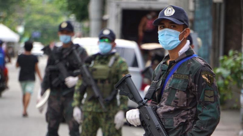Armed policemen man a checkpoint along a road in Cebu City, central Philippines. (AFP)