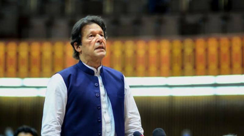 Pakistan's Prime Minister Imran Khan (L) speaks during the National Assembly session in Islamabad. (Handout photograph released by the Pakistan's Press Information Department)