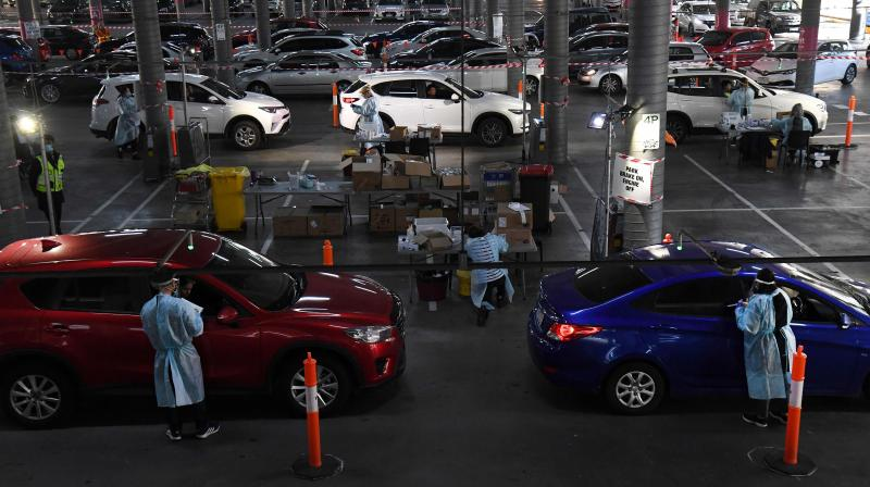 Medical workers staff a drive-through Covid-19 testing site located in a shopping centre carpark in Melbourne. (AFP)