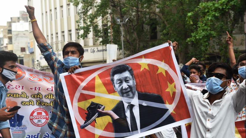 Activists of Gujarat's Karni Sena organisation shout slogans while holding a poster with the image of Chinese President Xi Jinping during an anti-China demonstration in Ahmedabad on June 24, 2020. (AFP)