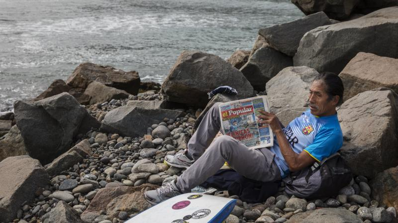 A man reads a newspaper next to the Pacific Ocean on the coast of Lima, Peru. (AP)