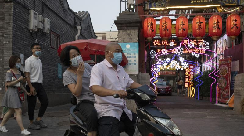 Residents wearing masks to curb the spread of the coronavirus past by lanterns and neon lights promoting a restaurant in Beijing. (AP)