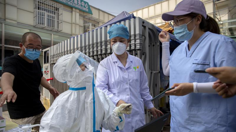 A worker wearing a protective suit talks with people registering for coronavirus tests at a community health clinic in Beijing, Sunday, June 28, 2020.(AP)