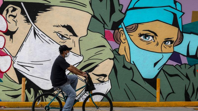 A man ride sa bike past a coronavirus-related mural by urban artists Mick Martinez and
