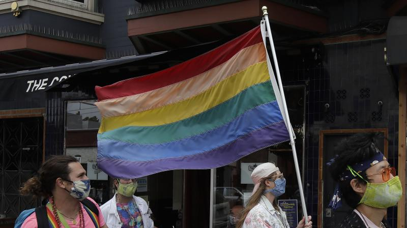 Zina Goodall wears a face mask as she carries a rainbow flag while walking with friends in the Castro District amid the coronavirus outbreak in San Francisco, Saturday, June 27, 2020. (AP)