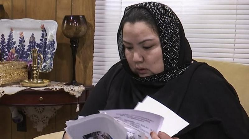 In this image from video, Zumret Dawut, a Uighur from China's far western Xinjiang region, holds documents she brought with her, at her new home in Woodbridge, Va., on Monday, June 15, 2020. Dawut says in China, she was forcibly sterilized for having a third child after being released from a Xinjiang detention camp. (AP)