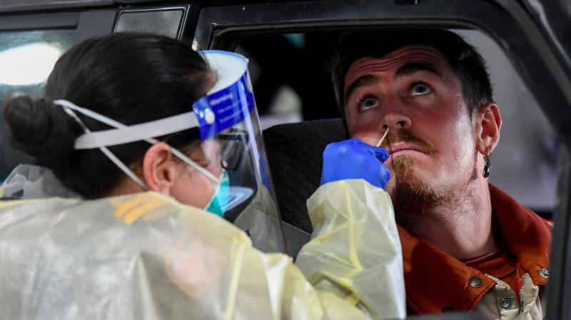 A member of the Australian Defence Force (L) takes a swab for a COVID-19 coronavirus test on a member of the public in Melbourne on June 27, 2020. (AFP)