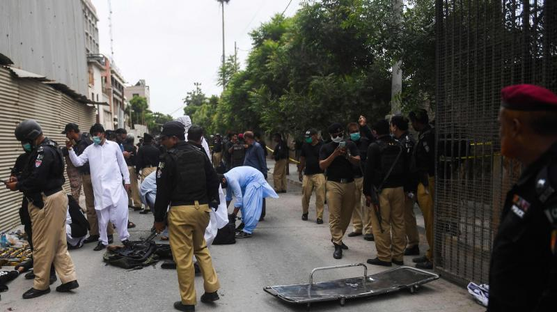 Police collect evidence next to the bodies of alleged gunmen outside the Pakistan Stock Exchange building in Karachi on June 29, 2020.(AFP)